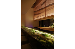プリザーブドフラワーの苔を使用して制作されたダイニング席と、苔と石で日本庭園をイメージした窓の外